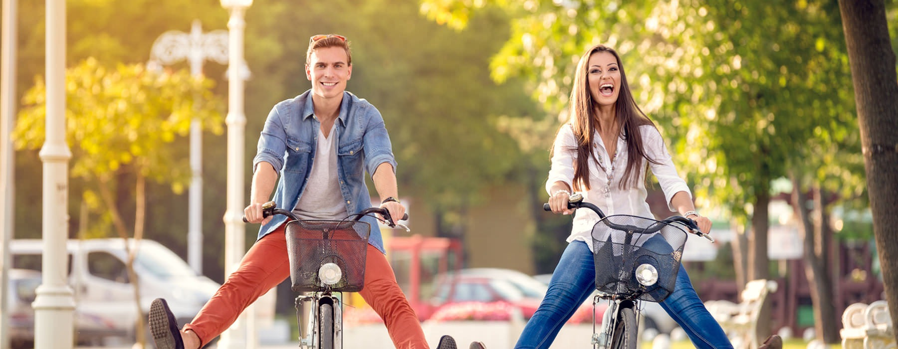 guy and girl being silly with legs outstretched on their bicycles as they ride through a neighborhood park